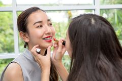 De vrouw neemt lippenstift in ruimte Vrienden die samenstelling in ruimte doen Lippenstift royalty-vrije stock fotografie