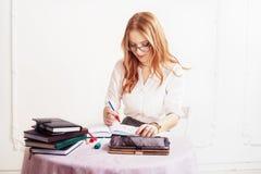 De vrouw neemt nota's in blocnote Het concept zaken, banen, edu Stock Afbeelding