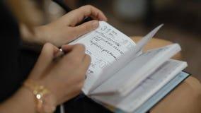 De vrouw neemt nota's in een notitieboekje stock videobeelden