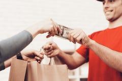 De vrouw neemt Pakket van Koerier en geeft Contant geld royalty-vrije stock afbeelding