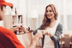 De vrouw neemt Pakket van Koerier en geeft Geld stock foto