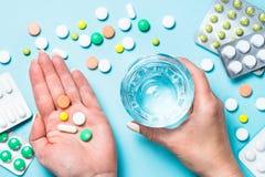 De vrouw neemt pillen op blauwe hoogste mening stock foto's