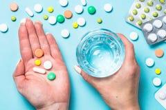 De vrouw neemt pillen op blauwe hoogste mening stock afbeelding