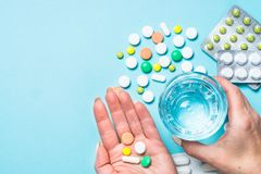 De vrouw neemt pillen op blauwe hoogste mening royalty-vrije stock afbeelding