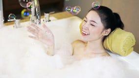 De vrouw neemt schuimbad en het spelen in badkuip stock videobeelden