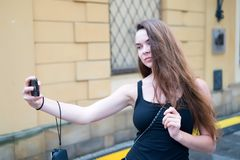 De vrouw neemt selfie met mobiele telefoon op straat Vrouw met lange smartphone van het haargebruik op stedelijke openlucht Het m stock afbeeldingen