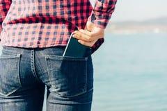 De vrouw neemt smartphone van haar achterzak van jeans Royalty-vrije Stock Foto