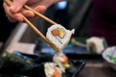 De vrouw neemt Uramaki-sushibroodje met de verse die zalm, avocado en kaas van Philadelphia op, met sesamzaden wordt behandeld royalty-vrije stock foto