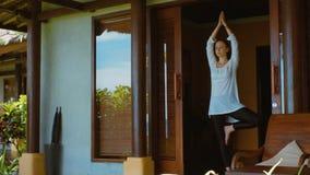 De vrouw oefent yoga in boompositie, het mediteren en rek uit, op de portiek van bungalow op het strand in Bali, aardgeluiden stock video