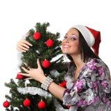 De vrouw omhelst een Kerstmisboom Stock Foto's