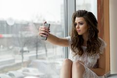 De vrouw in ondergoed op venstervensterbank maakt selfie royalty-vrije stock foto's
