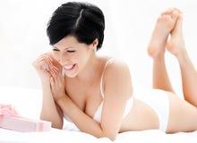 De vrouw in ondergoed vindt een verrassing in bed Royalty-vrije Stock Foto