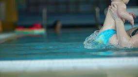 De vrouw onderwijst zijn jonge zoon om in de pool te duiken Het kind heeft een verrast gezicht Het versterken van immuniteit, de  stock video