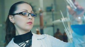 De vrouw onderzoekt fles in een laboratorium stock footage