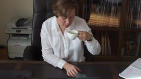 De vrouw onderzoekt de telefoon, drinkt koffie stock video