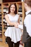 De vrouw ontmoet meer sommelier in een alcoholische drankwinkel royalty-vrije stock fotografie