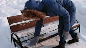 De vrouw ontruimt de bank in de loop van de dag van sneeuw in het park van de de winterstad in sneeuwweer met dalende sneeuw stock videobeelden