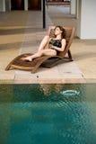 De vrouw ontspant door de poolkant stock afbeelding
