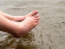 De vrouw ontspant door de rivierzitting, slingert haar voeten aan de waterspiegel stock fotografie
