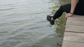 De vrouw ontspant door de meerzitting op de rand van een houten pier stock videobeelden