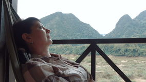 De vrouw ontspant in een hangmat stock video