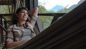 De vrouw ontspant in een hangmat stock videobeelden