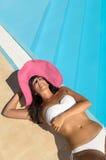 De vrouw ontspant het zonnebaden bij poolside Royalty-vrije Stock Afbeelding