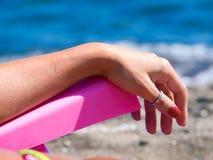 De vrouw ontspant op een ligstoel, strand, die het overzees onder ogen zien Stock Afbeeldingen