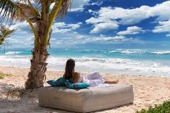 De vrouw ontspant op een tropisch strand stock afbeelding