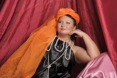 De vrouw in oosterse robes legt lui op hoofdkussens royalty-vrije stock foto's