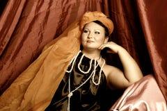 De vrouw in oosterse robes legt lui op hoofdkussens stock afbeeldingen