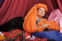De vrouw in oosterse robes legt lui op hoofdkussens stock fotografie