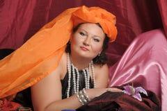 De vrouw in oosterse robes legt lui op hoofdkussens royalty-vrije stock afbeelding