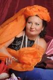 De vrouw in oosterse robes legt lui op hoofdkussens royalty-vrije stock afbeeldingen