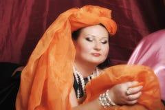 De vrouw in oosterse robes legt lui op hoofdkussens stock foto