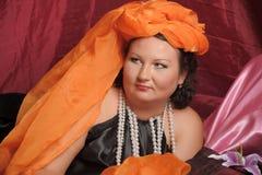 De vrouw in oosterse robes legt lui op hoofdkussens stock foto's