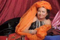 De vrouw in oosterse robes legt lui op hoofdkussens stock afbeelding