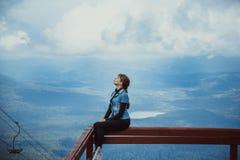 De vrouw op de achtergrond van bergen zit Stock Afbeeldingen