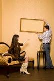 De vrouw op bank en de man hangen omhoog op muurbeeld Royalty-vrije Stock Foto's