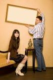 De vrouw op bank en de man hangen omhoog op muurbeeld Stock Foto