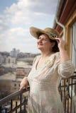 De vrouw op een balkon, glimlacht en bekijkt de hemel Stock Fotografie
