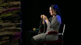 De vrouw op een zwarte achtergrond breit op cirkelnaalden van gele draad stock video