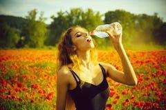 de vrouw op gebied van papaverzaad drinkt water van fles royalty-vrije stock afbeelding