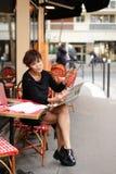 De vrouw op middelbare leeftijd bespreekt nieuwe uitgave van krant stock fotografie