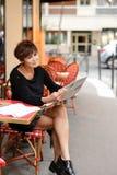 De vrouw op middelbare leeftijd bespreekt nieuwe uitgave van krant stock afbeelding
