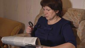 De vrouw op middelbare leeftijd leest een krant door een vergrootglaszitting als voorzitter stock afbeeldingen