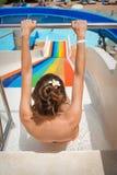 De vrouw op waterdia bij een waterpark wil zich uit bewegen Stock Foto's