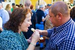 De vrouw opende haar mond De man voedt een fondue van de vrouwenkaas met een lepel Witte gesmolten kaasrek In een ceramische pot royalty-vrije stock foto