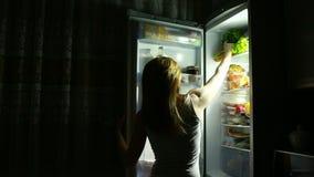 De vrouw opent de ijskast bij nacht Nachthonger Dieet Het eten van sandwich stock footage