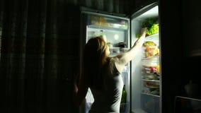 De vrouw opent de ijskast bij nacht Nachthonger Dieet Het eten van sandwich stock videobeelden